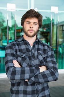 Homem jovem sério em pé ao ar livre com os braços cruzados