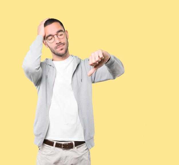 Homem jovem sério, fazendo um gesto de derrotado