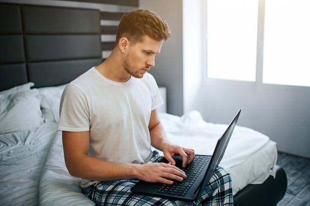 Homem jovem sério na cama esta manhã. ele trabalha em casa tipo de cara no teclado do laptop e olhar para a tela. luz do dia.