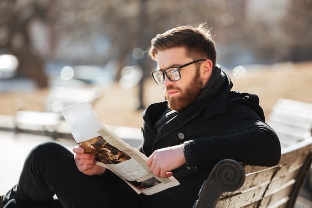 Homem jovem sério sentado e lendo jornal na cidade