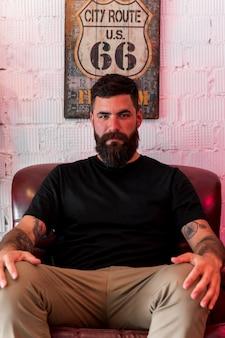 Homem jovem sério sentado na poltrona no salão de beleza