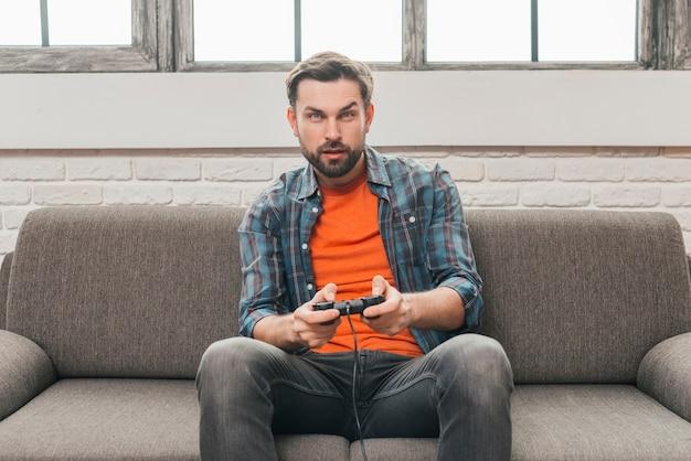 Homem jovem sério sentado no sofá jogando videogame