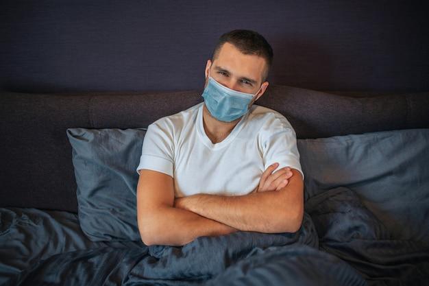 Homem jovem sério usa máscara de proteção. ele senta na cama e olha para a câmera. cara mantém as mãos cruzadas. ele é muito sério.