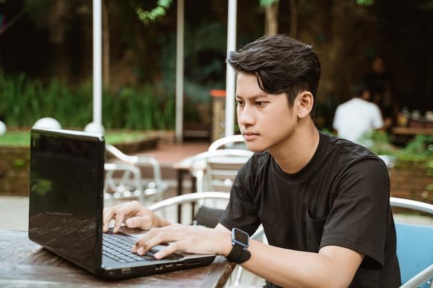 Homem jovem sério usando um laptop