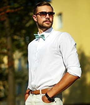 Homem jovem sexy bonito modelo elegante no estilo de vida casual de pano na rua de óculos
