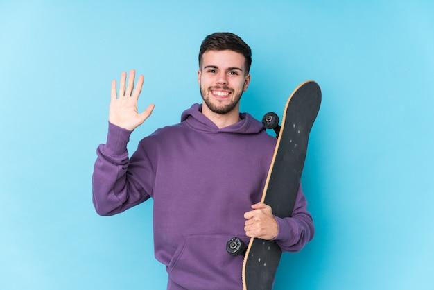 Homem jovem skatista isolado sorrindo alegre mostrando o número cinco com os dedos