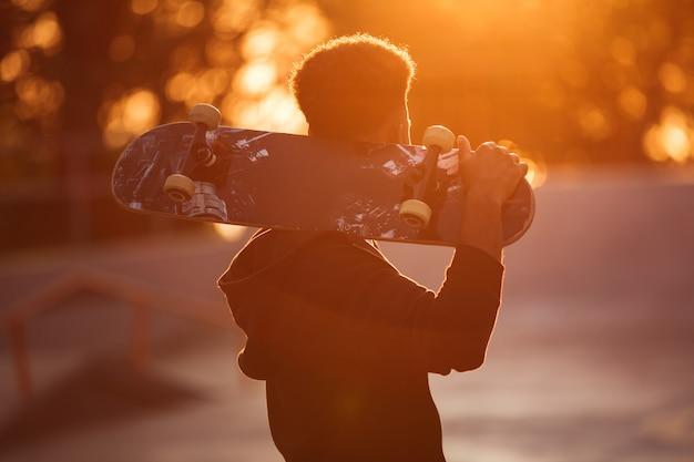 Homem jovem skatista segurando o skate