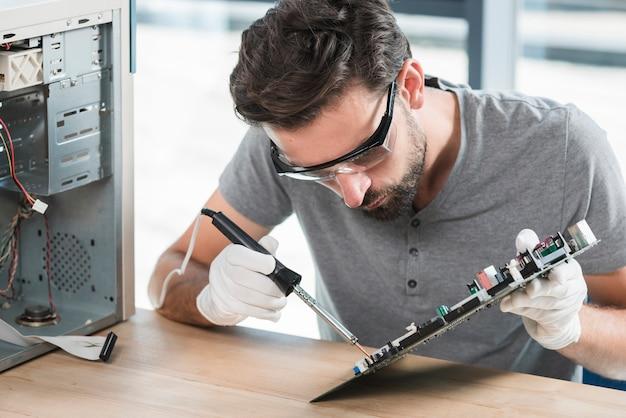Homem jovem, soldar, circuito computador, sobre, escrivaninha madeira