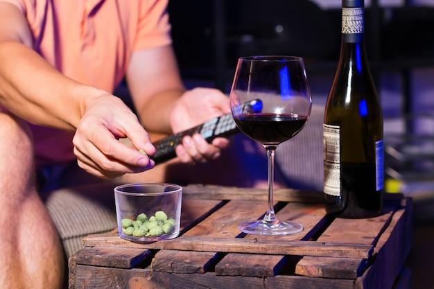 Homem jovem, solteiro, sentado em um sofá, bebendo vinho e comendo lanches não saudáveis e assistindo filme, série, programa de tv tarde da noite.