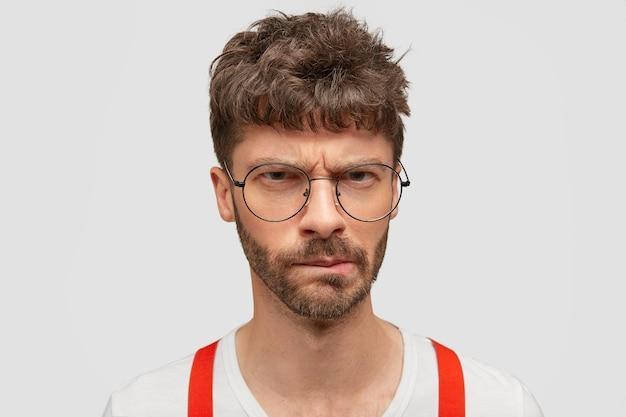 Homem jovem sombrio com a barba por fazer, com cerdas, sente-se infeliz, expressa emoções negativas, sente-se insatisfeito