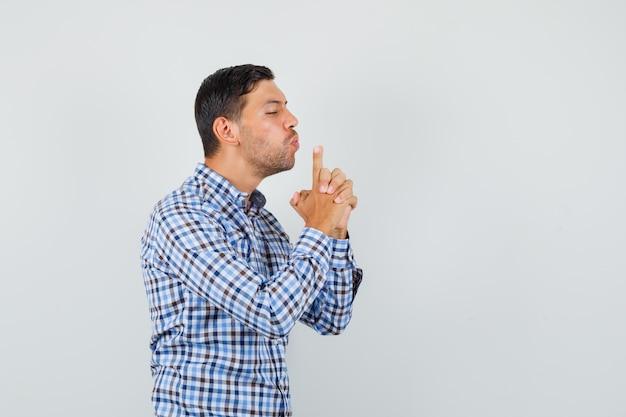 Homem jovem soprando uma arma feita à mão em uma camisa xadrez e parecendo confiante
