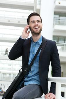 Homem jovem, sorrindo, com, telefone móvel