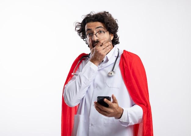 Homem jovem super-herói caucasiano chocado com óculos ópticos, uniforme de médico com capa vermelha e estetoscópio no pescoço, coloca a mão na boca e segura o telefone isolado na parede branca