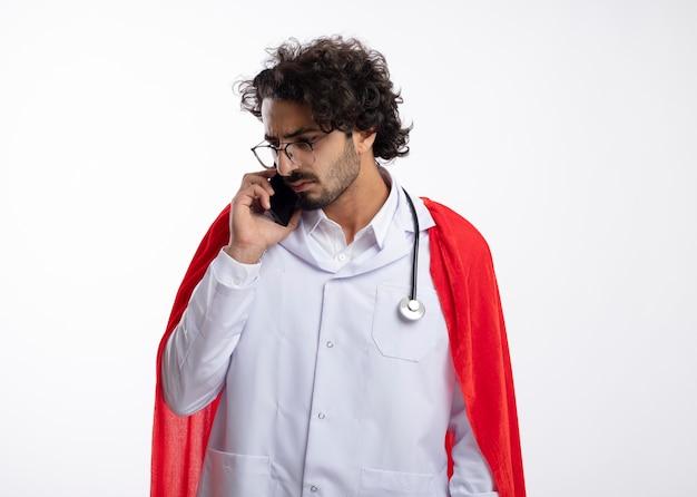 Homem jovem super-herói caucasiano confiante em óculos ópticos, usando uniforme de médico com capa vermelha e com estetoscópio no pescoço, fala no telefone olhando para o lado isolado na parede branca