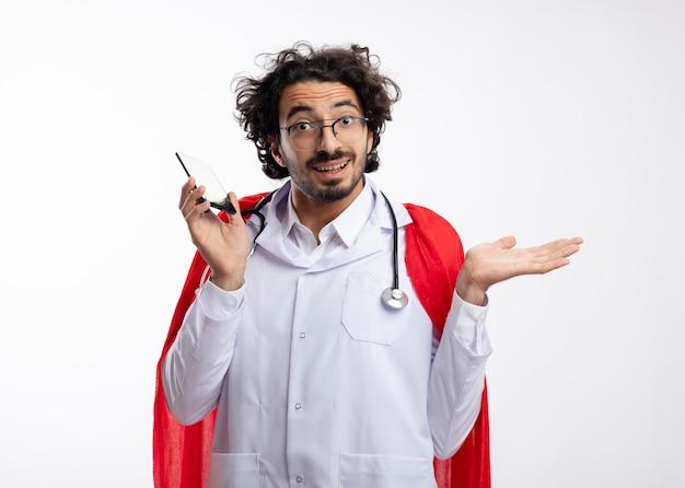 Homem jovem super-herói caucasiano impressionado com óculos ópticos, uniforme de médico com capa vermelha e estetoscópio no pescoço, mantém a mão aberta e segura o telefone com espaço de cópia