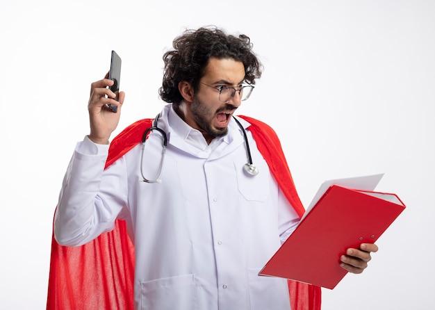 Homem jovem super-herói caucasiano irritado com óculos ópticos, usando uniforme de médico com capa vermelha e com estetoscópio no pescoço segura o telefone e olha para a pasta de arquivo na parede branca