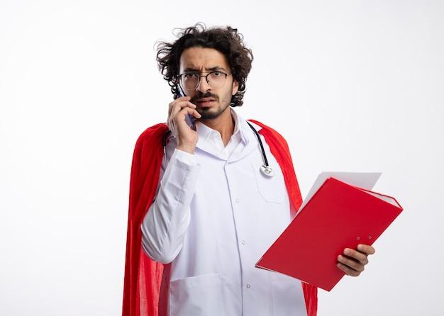 Homem jovem super-herói caucasiano sem noção com óculos ópticos, uniforme de médico com capa vermelha e estetoscópio no pescoço, fala no telefone e segura a pasta de arquivo com espaço de cópia