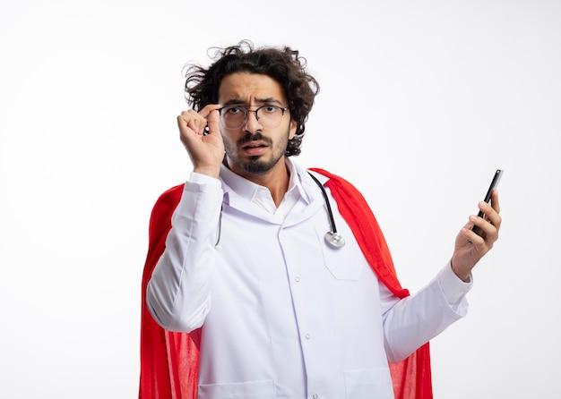 Homem jovem super-herói caucasiano sem noção com óculos ópticos, uniforme de médico com capa vermelha e estetoscópio no pescoço segura o telefone e parece com espaço de cópia