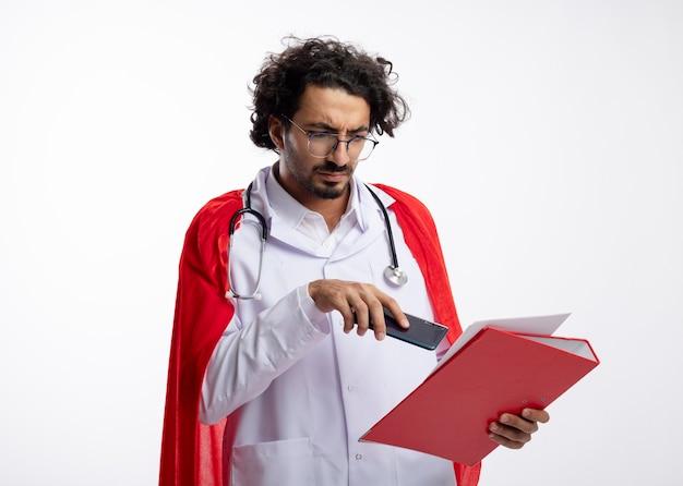 Homem jovem super-herói caucasiano sério com óculos ópticos, uniforme de médico com capa vermelha e estetoscópio no pescoço, aponta para pasta de arquivo com telefone com espaço de cópia