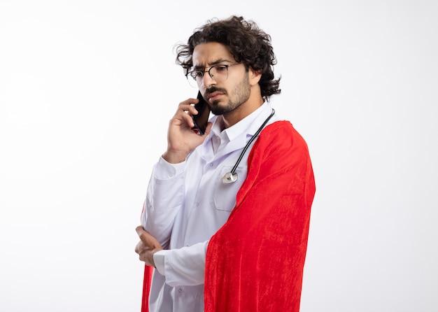 Homem jovem super-herói caucasiano sério com óculos ópticos, uniforme de médico com capa vermelha e estetoscópio no pescoço fica de lado falando ao telefone com espaço de cópia
