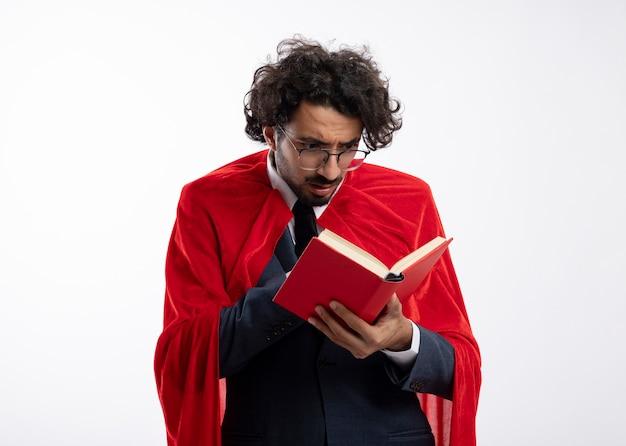 Homem jovem super-herói chocado usando óculos óticos, vestindo um terno com capa vermelha, segura e olha para o livro isolado na parede branca