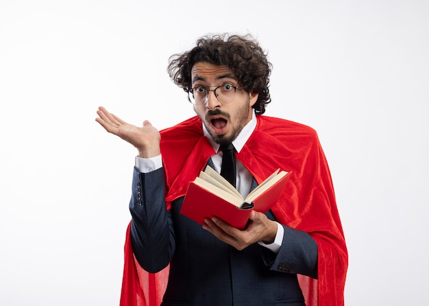 Homem jovem super-herói surpreso em óculos ópticos, usando terno com capa vermelha, fica com a mão levantada e segura o livro isolado na parede branca