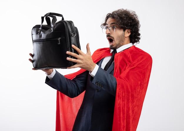 Homem jovem super-herói surpreso usando óculos ópticos, usando um terno com capa vermelha, segura e olha para a bolsa de couro isolada na parede branca