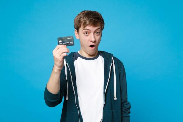 Homem jovem surpreso espantado com roupas casuais, segurando o cartão do banco de crédito, mantendo a boca bem aberta, isolada na parede azul. emoções sinceras de pessoas, conceito de estilo de vida.