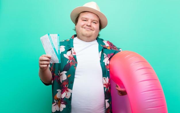 Homem jovem tamanho grande com um donut inflável na parede plana