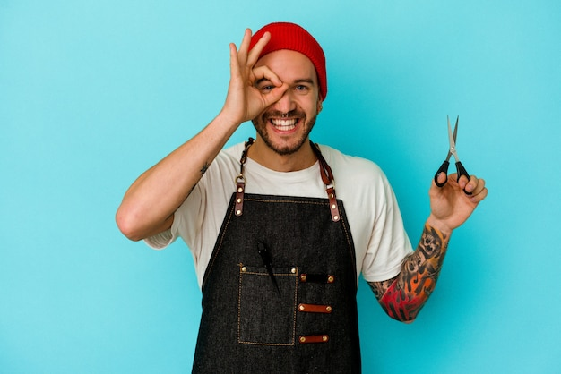 Homem jovem tatuado barbeiro isolado em um fundo azul animado, mantendo o gesto ok no olho.