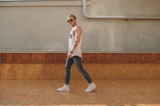 Homem jovem tatuado hipster com óculos de sol andando