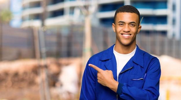 Homem jovem trabalhador afro-americano, apontando para o lado para apresentar um produto em um canteiro de obras