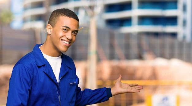 Homem jovem trabalhador afro-americano, apontando para trás e apresentando um produto em um canteiro de obras