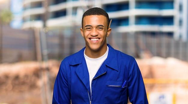 Homem jovem trabalhador afro-americano feliz e sorridente em um canteiro de obras