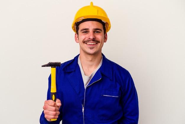 Homem jovem trabalhador caucasiano segurando um martelo isolado no fundo branco feliz, sorridente e alegre.