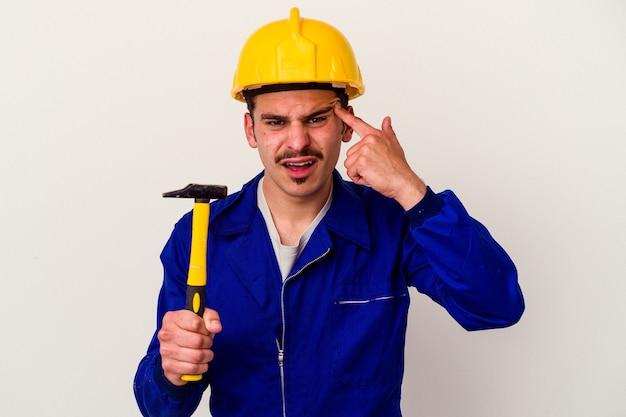 Homem jovem trabalhador caucasiano segurando um martelo isolado no fundo branco, mostrando um gesto de decepção com o dedo indicador.