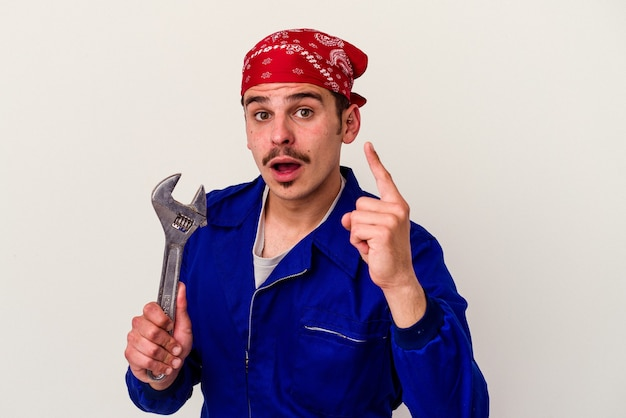 Homem jovem trabalhador caucasiano segurando uma chave inglesa isolada no fundo branco, tendo uma ideia, o conceito de inspiração.