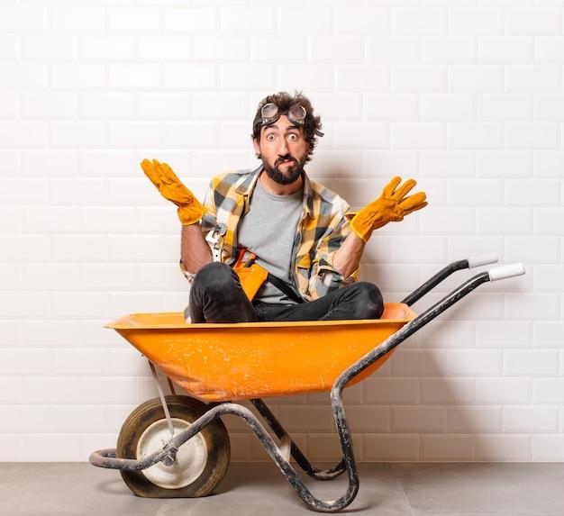 Homem jovem trabalhador da construção civil barbudo em um carrinho de mão