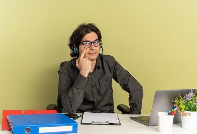 Homem jovem trabalhador de escritório confiante com fones de ouvido em óculos ópticos sentado na mesa com ferramentas de escritório usando laptop aponta para o olho
