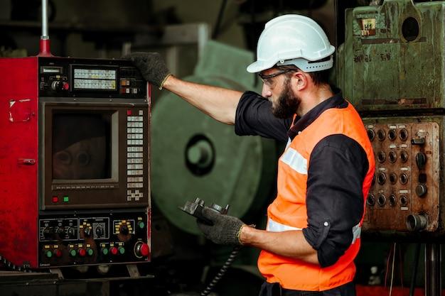 Homem jovem trabalhador industrial trabalhando com máquina de metal em fábrica com muitos equipamentos