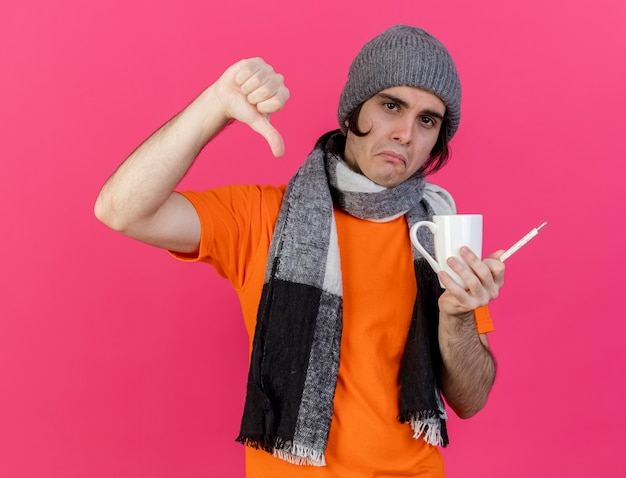 Homem jovem triste e doente com chapéu de inverno e lenço segurando uma xícara de chá com termômetro mostrando o polegar para baixo isolado no fundo rosa