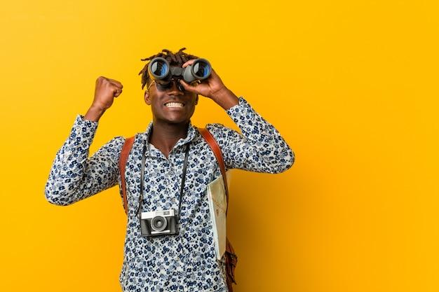 Homem jovem turista africano em pé contra um amarelo segurando um binóculo