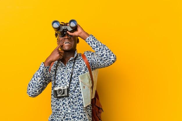 Homem jovem turista africano em pé segurando um binóculo