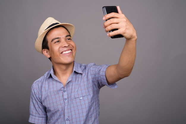 Homem jovem turista asiática usando chapéu pronto para férias contra parede cinza