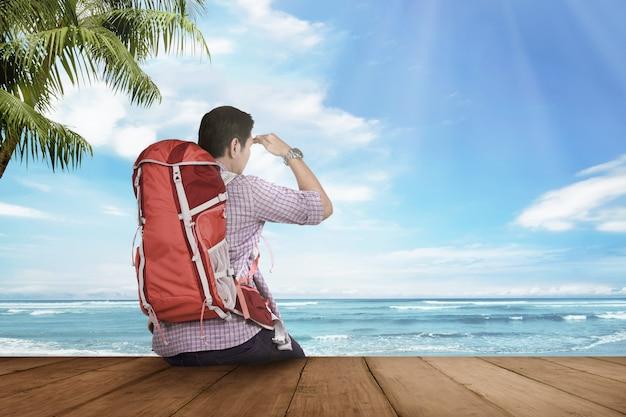 Homem jovem turista asiático sentado e olhando para a paisagem