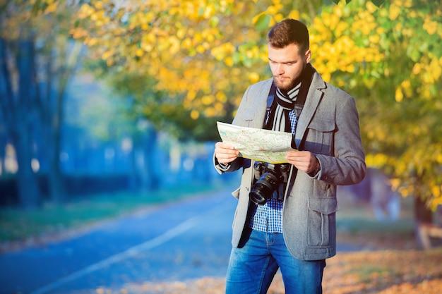 Homem jovem turista com mapa e câmera