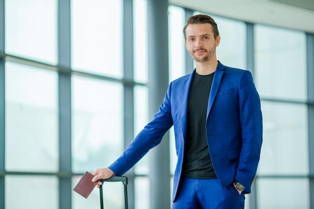 Homem jovem turista com passaporte e cartão de embarque no aeroporto pronto para viajar