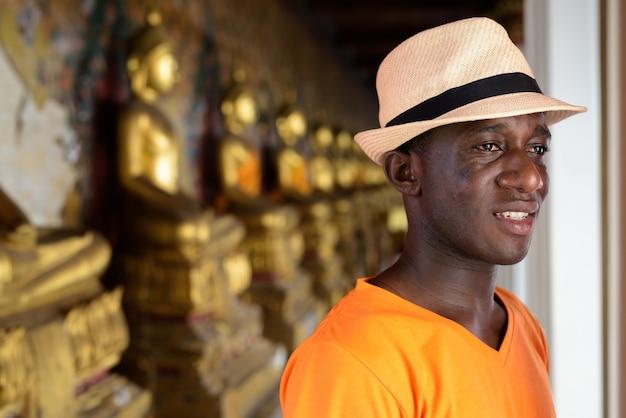 Homem jovem turista feliz sorrindo enquanto pensava contra a vista das estruturas alinhadas de buda no templo de wat arun