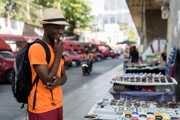 Homem jovem turista feliz sorrindo enquanto pensava e escolher qual comprar nas ruas de bangkok tailândia