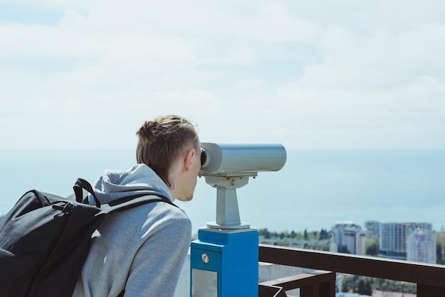 Homem jovem turista moderno olhando através de binóculos operados por moedas de metal no mar, céu e cidade, imagem horizontal de estoque de estilo de vida